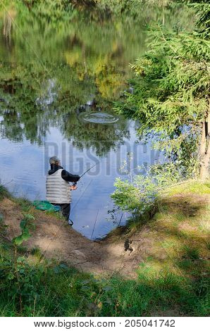 A fisherman woman is standing on the shore and throwing a fishing rod. The water shows the reflection of trees from the opposite shore