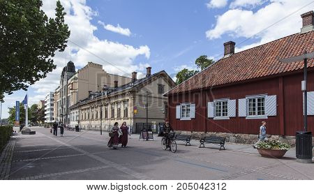 TURKU, FINLAND ON JUNE 30. Street view of old wooden buildings on the Medieval Market days on June 30, 2017 in Turku, Finland. Unidentified people move along the street. Editorial use.