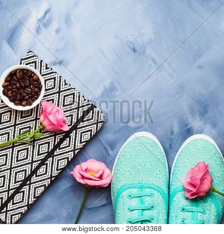 Flat lay with shoes, coffee and flowers on blue background. Copy space