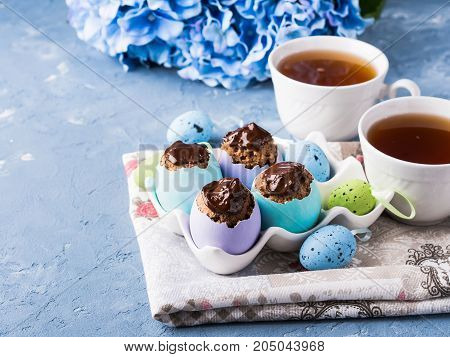 Easter sweet cup cakes treets in colorful pastel egg shells with chocolate and hydrangea flowers on blue background. Festive holiday home made food with cups of tea