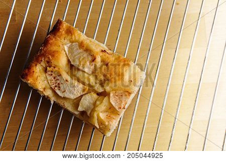 Piece of homemade apple cake on a baking grid over a light wooden table overhead view from above copy space selected focus