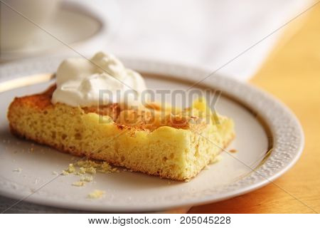 piece of homemade apple cake with whipped cream on a white plate close up copy space selected focus very narrow depth of field