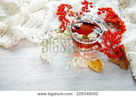A Cup of tea and Rowan berries on a wooden table. Autumn still-life. Autumn mood.