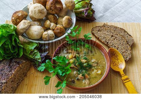 A plate of soup with mushrooms along with rye bread and greens.