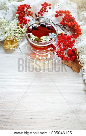 A Cup of tea and Rowan berries on a wooden table. Autumn still-life. Autumn mood.