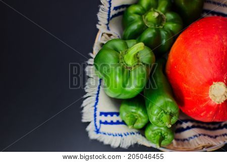 spot focus Organic Green bell pepper, Green paprika and pumpkin on black background with copy space