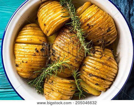 Potatoes baked with herbs in oven in enamel tin. Rustic style