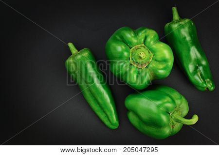 Organic Green bell pepper and Green paprika on black background with copy space