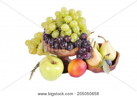 Light and dark grapes in a wooden bowl with an apple pear plum and figs on a white background.Fruit still life