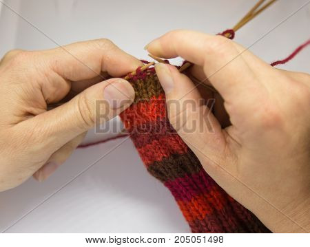 A woman knitting red woolen socks. Knitting close up on a white background. Hand crafts. Detailed view of a knitting skill.