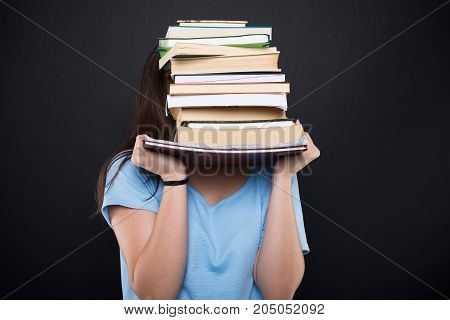 Young Student Hiding Behind Her School Books