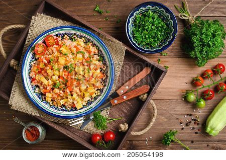 Rice pilaf with vegetables. Vegetarian dish with rice, carrots, onions, bell peppers, zucchini and lots of spices