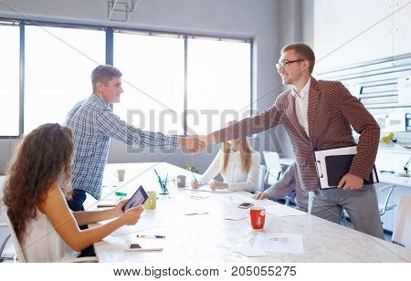 A successful young entrepreneur shaking hands with a student on a lecture on a conference room background. Business partnership programs.