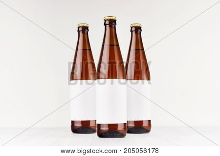 Three brown NRW beer bottles 500ml with blank white label on white wooden board mock up. Template for advertising design branding identity.
