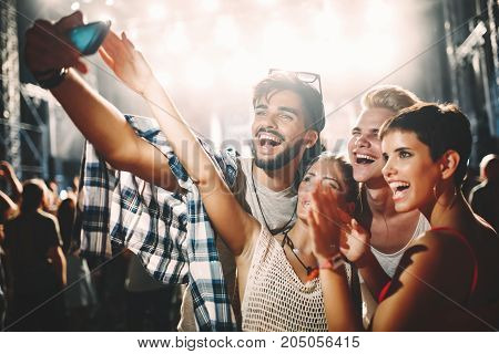 Happy young friends taking selfie at music festival