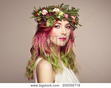 Beauty fashion model girl with colorful dyed hair. Girl with perfect makeup and hairstyle. Model with perfect healthy dyed hair. Flower wreath on head