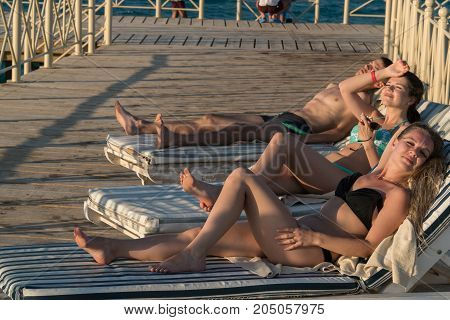 Friends sunbathe on the loungers on the pier. Soon the sunset.