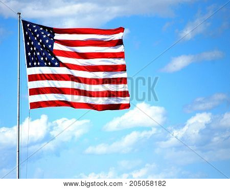 USA flag flying in the clear blue sky outdoors.