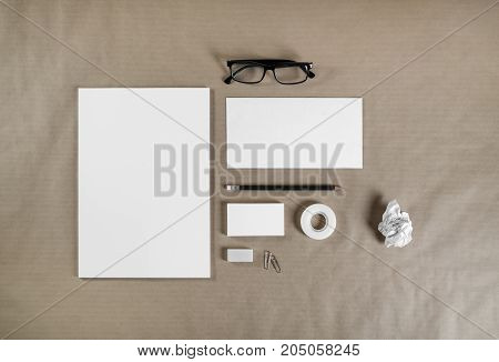 Photo of blank ID set. Stationery template on paper background. Branding mockup. Letterhead business cards envelope pencil glasses eraser and scotch tape. Top view.