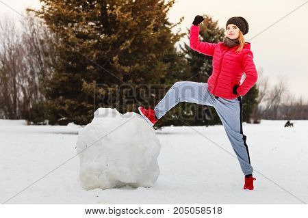 Woman wearing sportswear during winter weather with snow making big snowball for snowman