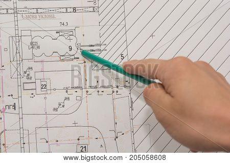 Closeup of man's hands holding blueprints at construction site