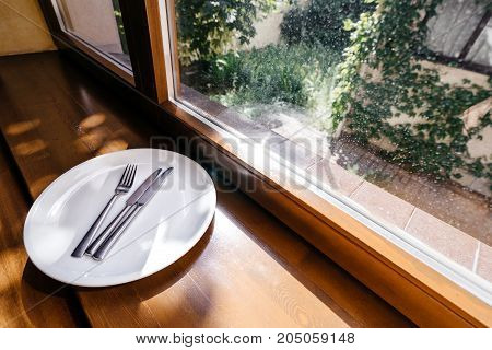 plate with Cutlery knife and fork are on the windowsill against the window with a view of the courtyard.