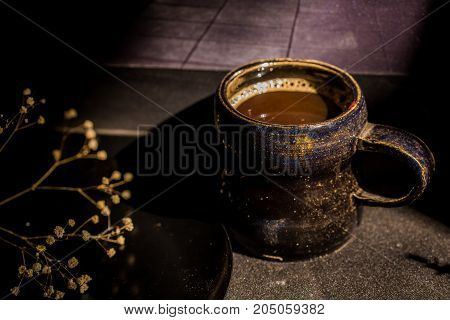 Close up stylish ceramic mug with coffee and a dry branch with flowers