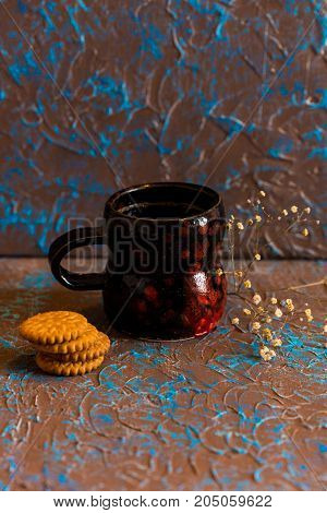 Vintage still life dark mug with coffee with several cookies and dry flower