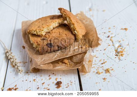 Close up freshly cooked oat cookie on paper on white wooden surface