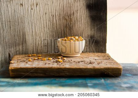 Close up round wooden bowl filled with dry corn grain