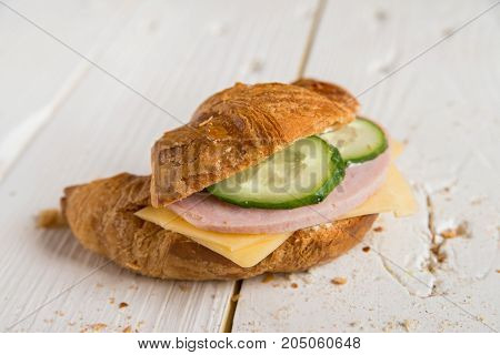 Close up delicious croissant stuffed with ham, cheese and fresh cucumber