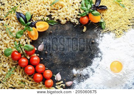 Layout of pasta and vegetables on a dark background