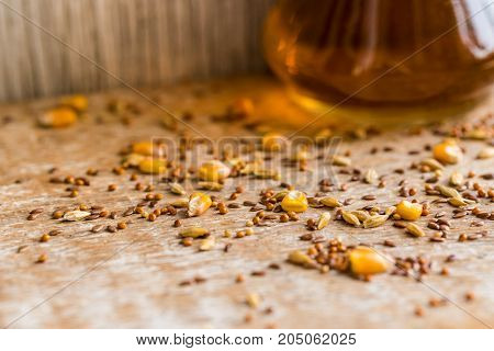 Close-up corn, linseed, oat, millet, wheat and barley grain scattered on surface and a decanter with seed oil organic food concept