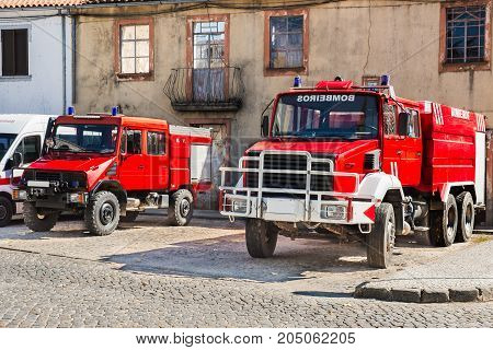 two Portuguese fire trucks parked on the street