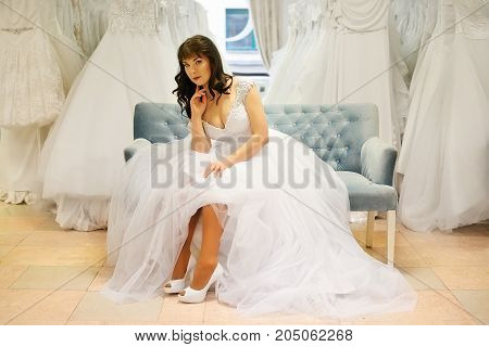 The bride shows beautiful legs on a blue sofa