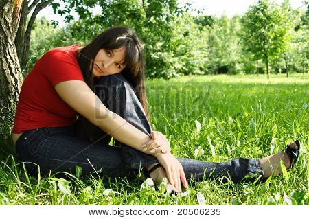 Young Brunette Girl In Red Shirt Siting Near Tree And Thinking, Summer Meadow