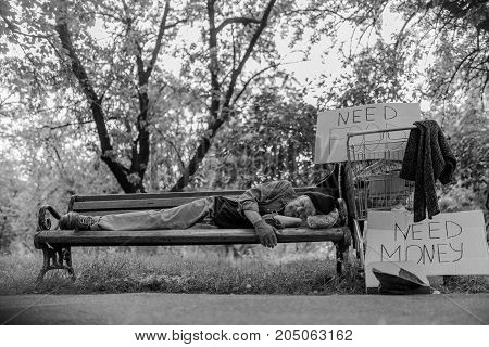 Black and white portrait of homeless man lying on bench. Man with no money and job, sleeping in the street.