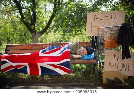 Sleeping homeless man covering with flag. Old man living in the streets, begging for help, money and food.