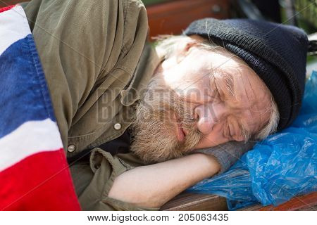 Close up portrait of homeless man sleeping on bench in city park. Poor aold male with no home and money living in the streets.