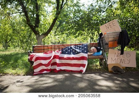 View of a homeless man lying on bench covered with USA flag. Poor man living in street, using USA flag as blanket.