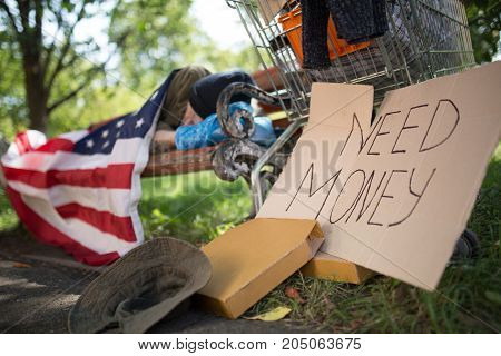 View of am old man, living in the streets. Homeless man sleeping on the bench, begging for money on card board.