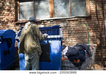 Poor old tramp in search for food or empty bottles. Way of life of old homeless man.