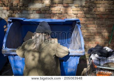 Homeless old man digging in trash can. Beggar collecting food and other staff in thrash can.