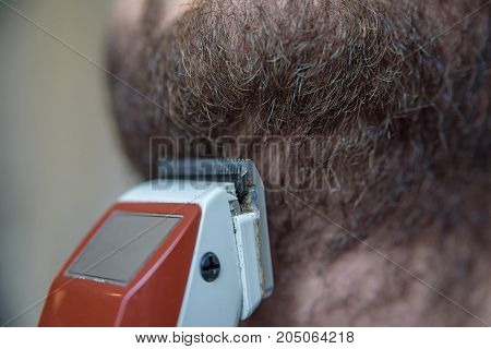 Close up image of dark beard and electric shaver