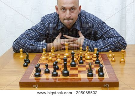 Man Playing Chess On Light Background. Closeup Of Young Man Thinking Over Move