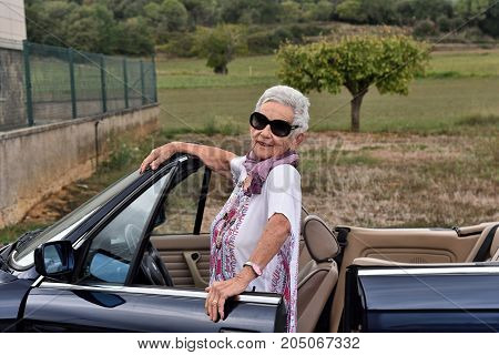 Portrait Of A Senior Woman With Convertible Car