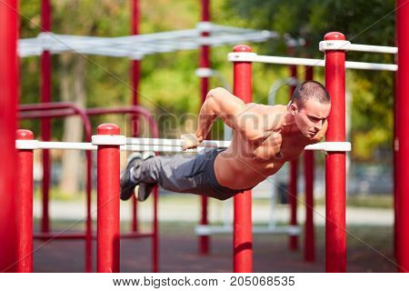 Full-length of strong athlete doing pull-up on horizontal bar. Mans fitness with blue sky in the background and open space around him.
