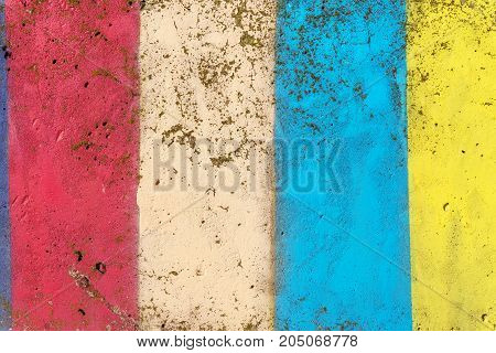 Concrete wall painted in colors of yellow, red and blue, abstract color background