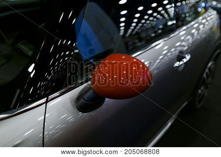 Red Left side Car mirror with reflection of a modern car. Car exterior details
