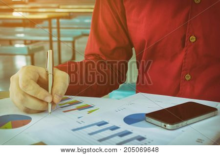 hand writing and working about cost with business strategy diagram report and mobile smart phone on desk at home office income and expenses finance plan money cost savings and economy concept